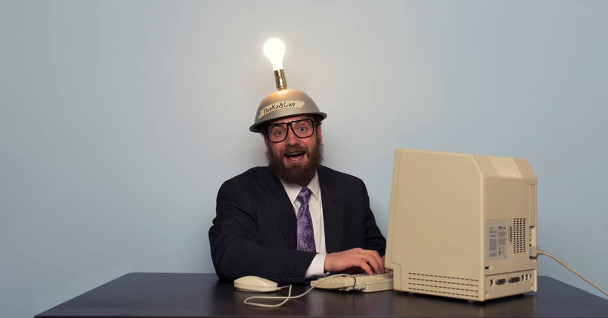 Male officer working grinning with lightbulb above his head while working on retro computer